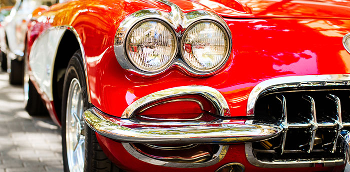 Specialist Cars: Close-up of the headlight of red classic car.